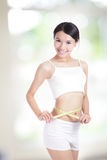 Woman measuring shape of waist with smile Royalty Free Stock Images