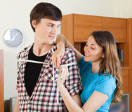 Woman measuring  shoulders  of boyfriend Royalty Free Stock Photos