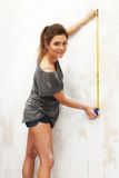Woman measuring spacing on a wall. Young beautiful brunette woman measuring spacing on a wall with roulette Royalty Free Stock Image