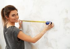 Woman measuring spacing on a wall. Young beautiful brunette woman measuring spacing on a wall with roulette Royalty Free Stock Photography