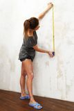 Woman measuring spacing on a wall Royalty Free Stock Image