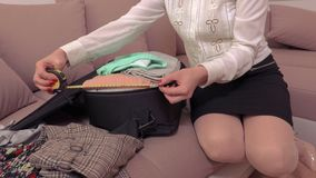 Woman measuring suitcase at home before journey. In room stock footage