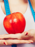 Woman with measuring tape around neck holding apple Royalty Free Stock Image