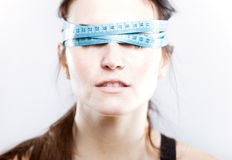 Woman with measuring tape covering her eyes Royalty Free Stock Images