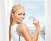 Woman with measuring tape and diet pills Stock Photography