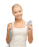 Woman with measuring tape and diet pills Royalty Free Stock Photos