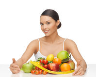 Woman with measuring tape and lots of fruits stock photography