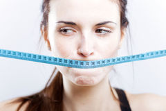Woman with measuring tape on mouth Royalty Free Stock Image