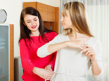 Woman measuring  waist of  girlfriend with measuring tap Royalty Free Stock Photos
