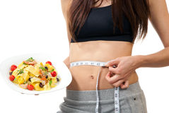 Woman measuring waist and holding diet food Stock Images