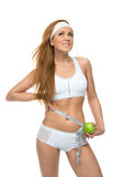 Woman measuring waist with tape measure and green apple emotions royalty free stock image