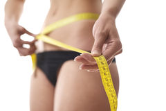 Woman measuring waist with tape on white background Royalty Free Stock Photos