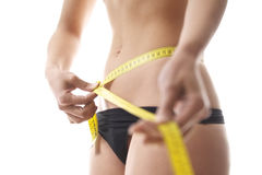 Woman measuring waist with tape on white background Stock Photo