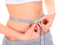 Woman measuring waistline. Woman measuring her perfect waistline with a white tape measure, isolated on white stock images