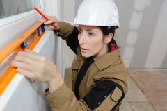 Woman measuring wall with spirit level in room. Woman measuring the wall with spirit level in room Stock Images