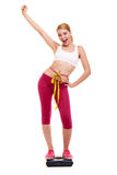 Woman measuring on weighing scale with raised arm. Royalty Free Stock Photos