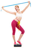 Woman measuring on weighing scale with raised arms Royalty Free Stock Photo
