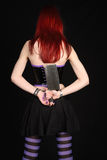 Woman with meat cleaver. Young redhead woman holding a meat cleaver behind her back stock photo