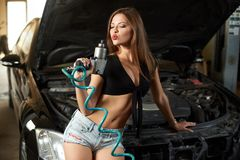 A woman mechanic blows off the dust from the screwdriver stock image
