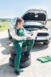 Woman mechanic with broken car and laptop.  stock photos