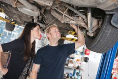 Woman and mechanic looking at car repairs Royalty Free Stock Photos