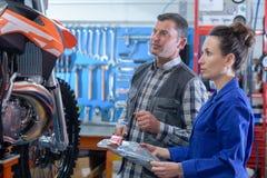 Woman mechanic repairing motorcycle in workshop royalty free stock photo