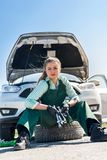 Woman mechanic sitting on spare wheel befor car stock photography