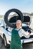Woman mechanic with tyre on shoulder and broken car. stock images