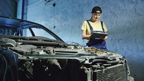 A woman mechanic uses a digital tablet in an auto repair garage. Mechanics overhauling an engine in the garage. Ordering new car parts via the Internet stock footage