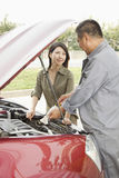 Woman and Mechanic Working on Car Royalty Free Stock Photography