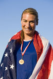 Woman With Medal Wrapped In American Flag. Portrait of happy female athlete with medal wrapped in American flag against sky Royalty Free Stock Image