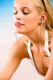 Woman with media player. Young beautiful happy smiling tanned blond woman in bikini with cellphone or media player on the beach Royalty Free Stock Image