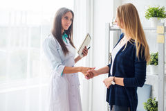 Woman medical doctor shaking hands with patient Royalty Free Stock Photo