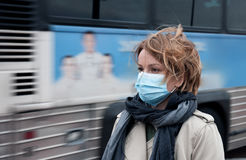 Woman with a medical face mask at outdoor. Portrait of woman walking on the street wearing protective mask as protection against infectious diseases Royalty Free Stock Image