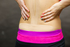 Woman with medical kinesio taping on back Stock Image