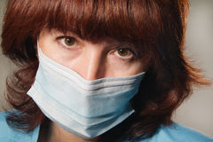 Woman in medical mask. Woman looks at camera in medical mask Royalty Free Stock Image