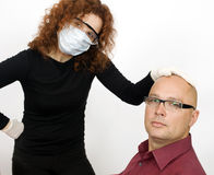Woman in medical mask keeps man for head Royalty Free Stock Image