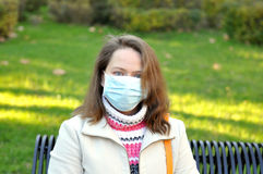 Woman in a medical mask on nature. Beautiful woman sitting on a park bench in a medical mask Stock Photography