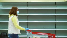 Woman in medical mask walking with shopping cart along empty shelves in store