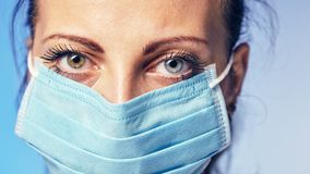 A woman in a medical mask. She has a serious facial expression Royalty Free Stock Photos