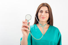 Woman in medical uniform holding stethoscope Stock Photo
