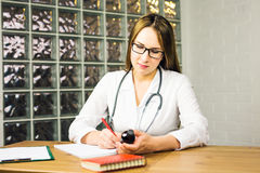 Woman medicine doctor hold jar of pills and write prescription to patient at worktable. Panacea and life save. Prescribing treatment, legal drug store concept Stock Images