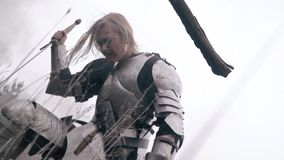 A woman knight in armor is kneeling in the field and experiencing grief, slow motion. Woman medieval armor is kneeling on the battlefield stock video footage