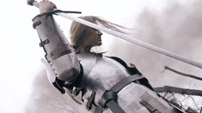 A woman in medieval armor is leaning on her sword and bowing her head. Tired woman knight in armor in smoke stock video