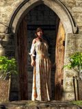 Woman at a Medieval Door. A woman in a flowery dress stands framed by the open door of an old stone building as if to either greet you or block your entrance stock illustration