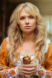 Woman in medieval dress. Beautiful blond woman in medieval dress walking near old building Royalty Free Stock Image