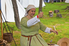 Woman in medieval setting and costume spinning yarn. Stock Image