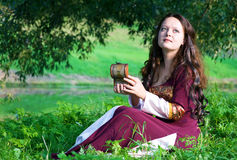 Woman in medieval suit with old casket. Young woman in medieval suit with old casket in hand sitting on the grass Stock Photos