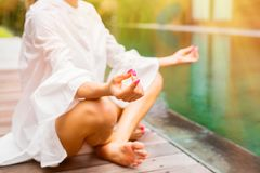 Woman meditate by the pool in the morning Royalty Free Stock Image