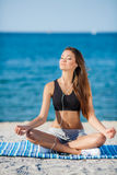 The woman meditates on a beach near the sea Royalty Free Stock Images
